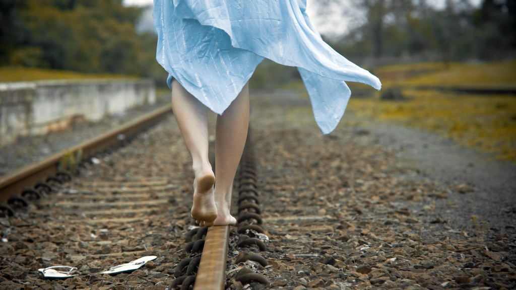 Young girl balances along a railway track in her blue dress